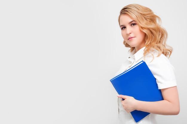 Женщина-врач с книгой, в медицинской форме на белой стене, с копией пространства. понятие медицинского образования, высшего образования, чтения книг и профессии врача.