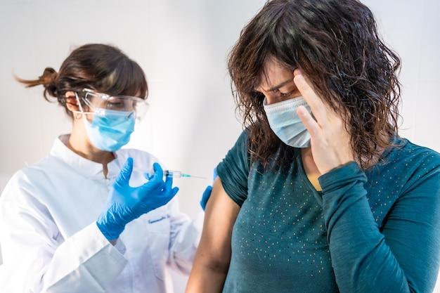 コロナウイルスワクチンを適用しているフェイスマスクを持った女性医師、ワクチンとその副作用を恐れている患者。