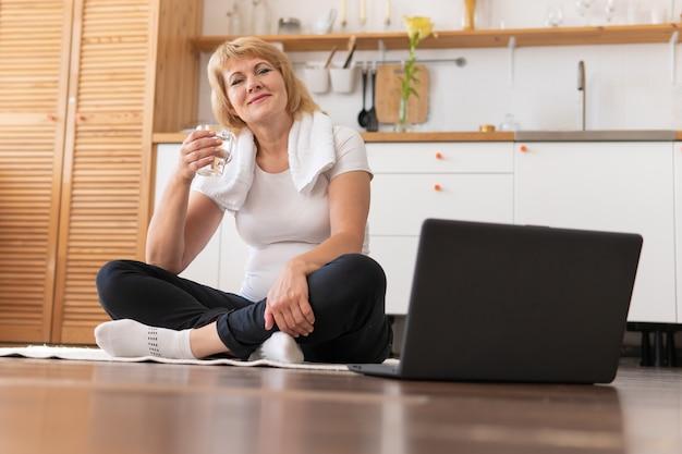 女性は家で体操をします。中年女性は明るい部屋でフィットネスをします。