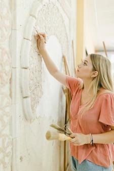 Женщина делает резьбу по стене