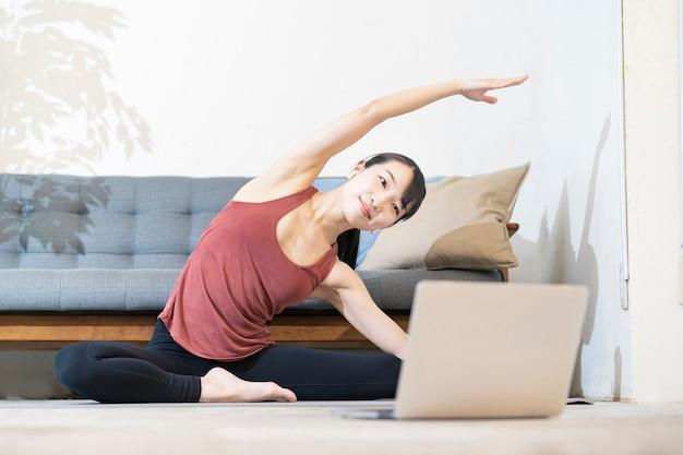 部屋のコンピューター画面を見ながらヨガをしている女性