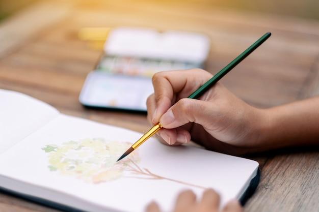 水彩で木の絵を描いて描く女性