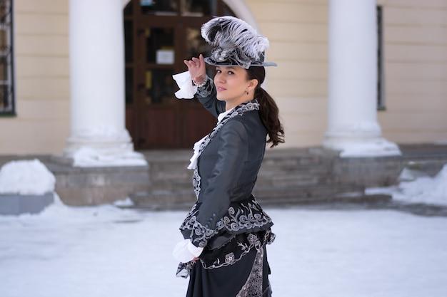 19세기 귀족 여성으로 분장한 여성이 오래된 저택 근처에 서 있습니다.러시아 겨울