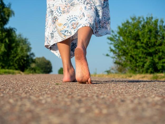 ドレスを着た女性が裸足でアスファルトの上を歩きます。背面図。旅行、レクリエーション、休暇、自由の概念