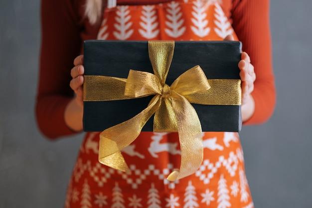 赤いドレスとクリスマスエプロンを着た女性が目の前にギフトボックスを持っています。