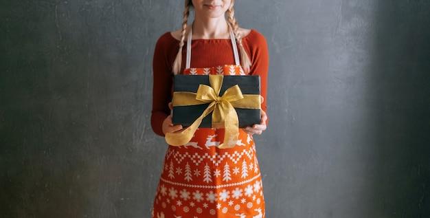 Женщина в красном платье и рождественском фартуке держит перед собой подарочную коробку.