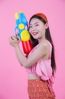 ピンク色の背景に水鉄砲を保持している伝統的なタイの民俗服を着た女性。