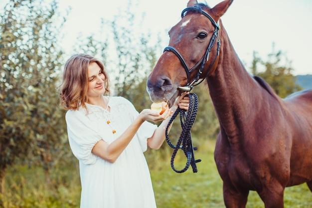 白いドレスを着た女性が赤いリンゴを馬に与える