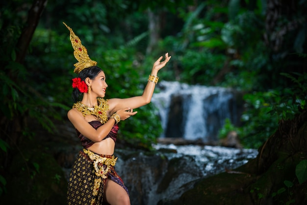 Женщина одета в старинное тайское платье у водопада.