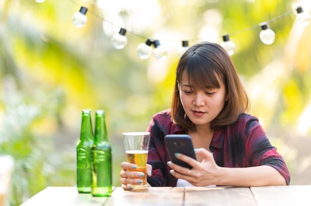 ビールを飲みながら電話で話している女性。