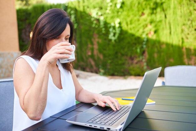 한 여성이 집 정원에서 노트북으로 재택근무를 하며 커피를 마신다