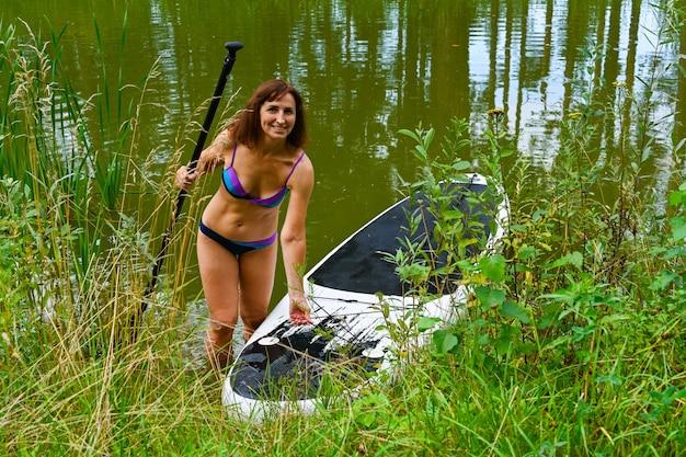 女性は、密集した草に囲まれた狭い運河を通ってサップボードをドライブします。アクティブな週末の休暇は、屋外の野生の自然です。女性が水着を着て上陸します。夏。