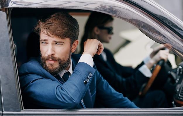 出張関係者の男性同僚の隣で車を運転している女性。