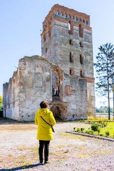 여행 중 한 여성이 고대 중세 성을 바라 봅니다.