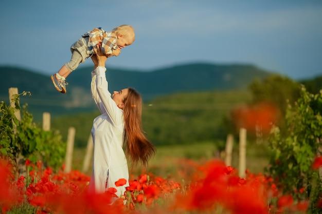 Женщина во время прогулки по лугу с цветами перебрасывает сына на голову