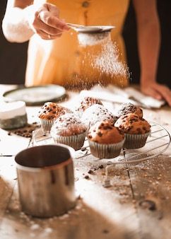 A woman dusting sugar on homemade muffins on cooling rack