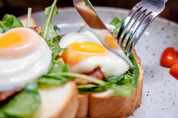 木製のテーブルの上の皿にナイフとフォークで卵、ベーコン、サワークリームと朝食サンドイッチを食べる女性