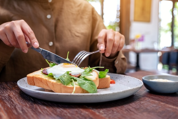 木製のテーブルの上の皿にナイフとスプーンで卵、ベーコン、サワークリームと朝食サンドイッチを食べる女性