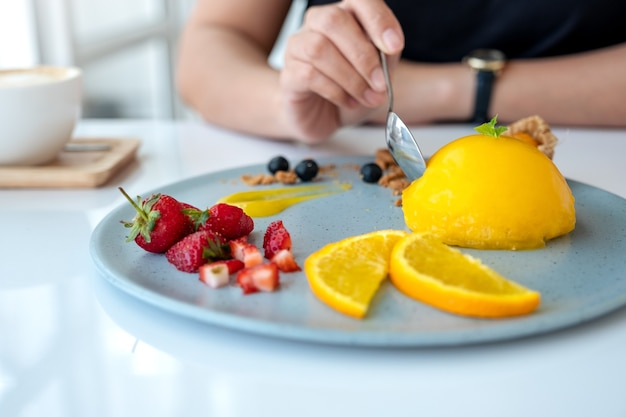 カフェでスプーンでミックスフルーツとオレンジのケーキを食べる女性
