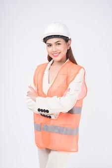 白い背景のスタジオの上に保護ヘルメットをかぶっている女性エンジニア