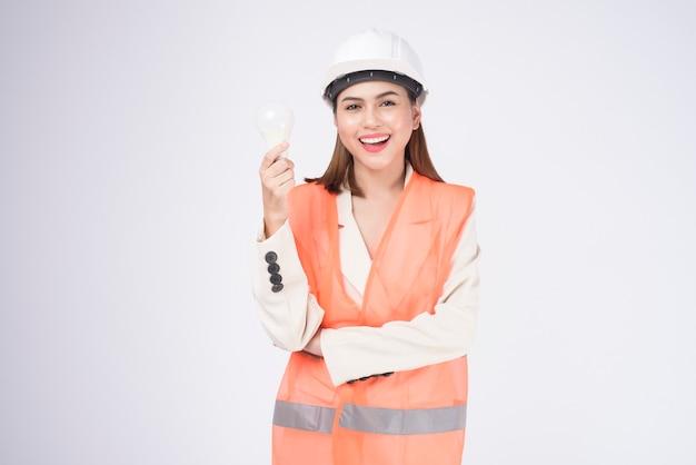 흰색 배경 스튜디오 위에 보호 헬멧을 쓴 여성 엔지니어