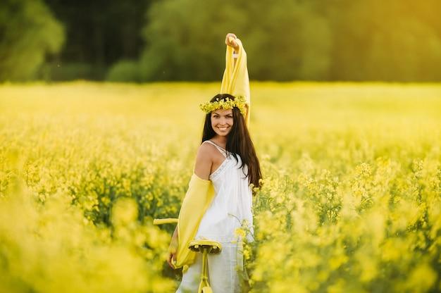 鮮やかな黄色の菜種がいっぱいの畑で自転車に乗る女性