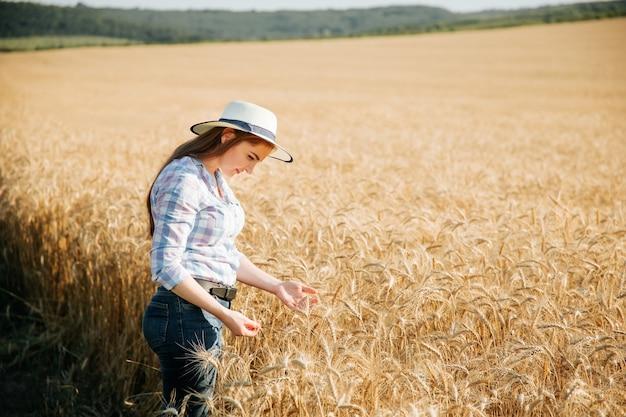 Женщина-фермер в шляпе, специалист по выращиванию растений, анализирует концепцию полевой пшеницы, экологию, биоинспекцию ...