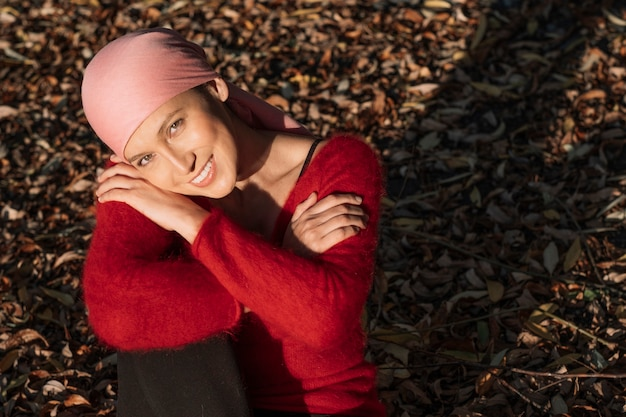 암과 싸우는 여자는 미소하고 카메라를 찾고 그녀의 무릎에 그녀의 팔을 앉아있다