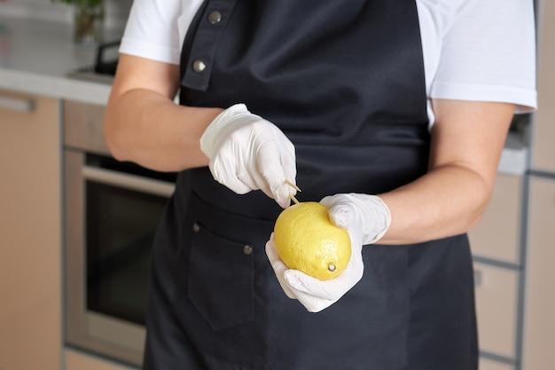 レモンをスティックに押し付けてフルーツブーケを空にする女性