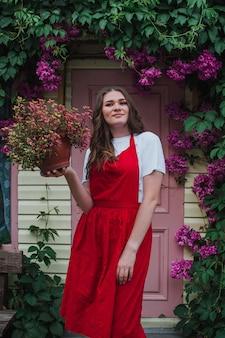 ピンクのドアを背景に花を手にした植木鉢を持っている女性の庭師