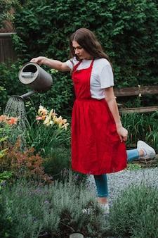 정원에 물을 주는 빨간 앞치마를 입은 여성 정원사