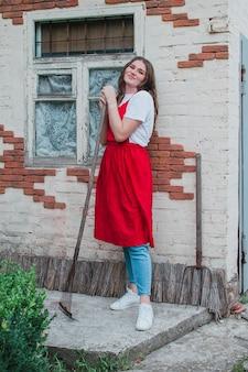 갈퀴를 든 여성 정원사는 시골 집 농업 개념의 배경에 서서
