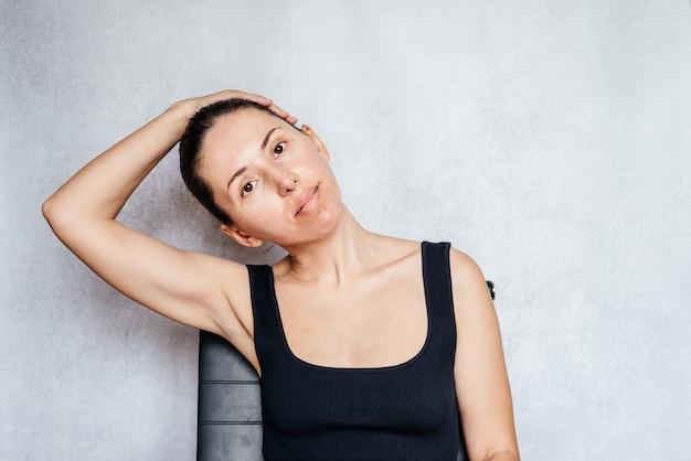 목 목 통증 완화를 위한 맥켄지 운동을 하며 부드럽게 머리를 잡아당기는 여성...