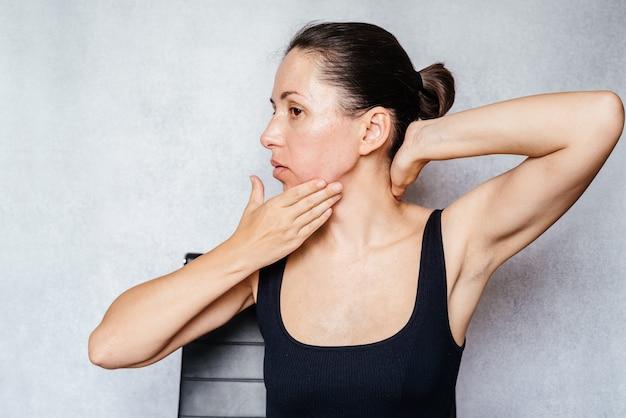 목에 mckenzie 방법 운동, 목 통증 완화 운동을하면서 여성이 양손으로 머리를 부드럽게 회전