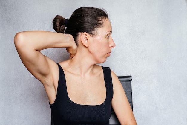 목에 맥켄지법 운동을 하면서 손으로 머리를 부드럽게 돌리는 여성...