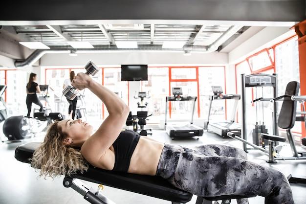 女の女の子が手を上げてトレーニング器具の上に横たわっています。彼女はダンベルで運動しています