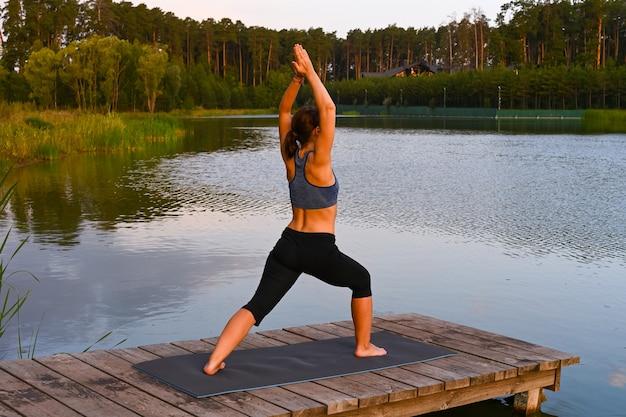 女性が湖でスポーツに出かけます。自然界の身体活動の概念。