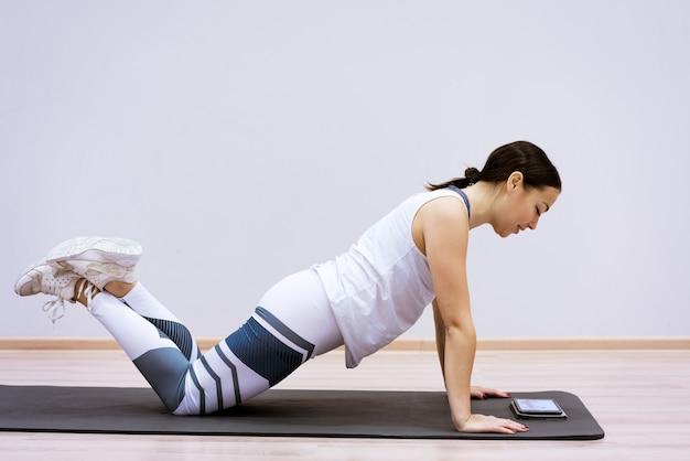 여자는 집을 떠나지 않고 태블릿 피트니스 클래스 개념 ss 운동에서 온라인 비디오를보고 스포츠에 간다