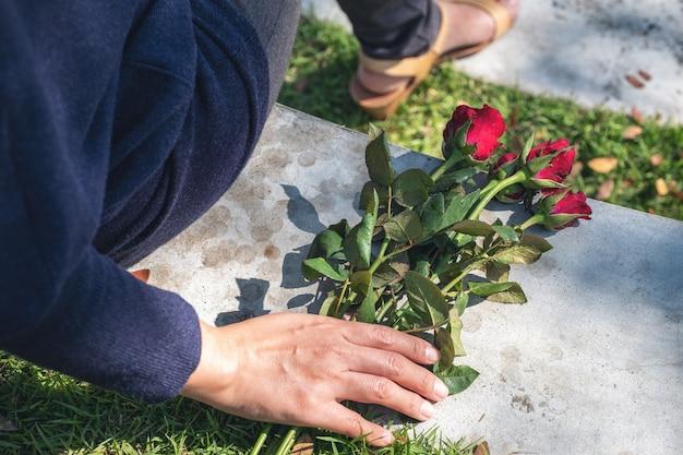 야외에 앉아있는 동안 땅에 빨간 장미 꽃을 잡고 들고있는 여자