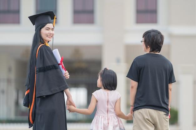 졸업식 날에 학위를 마친 여성 졸업생과 가족이 교육 성취를 축하합니다