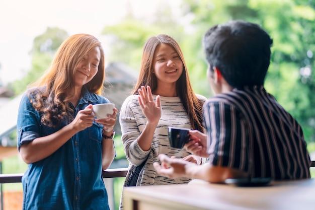 커피를 마시며 남자 친구들에게 인사하고 인사하는 여자