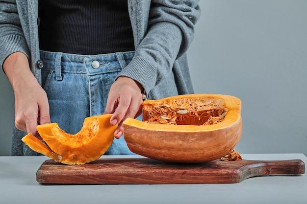 木の板の上でカボチャのスライスをナイフで切る女性の手。