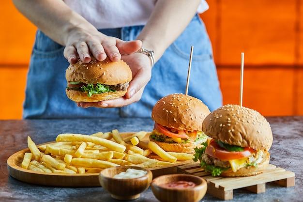 Женщина рука держит чизбургер с жареным картофелем, кетчупом, майонезом