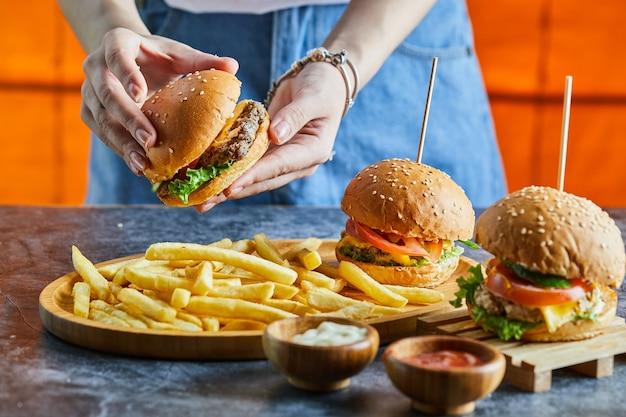 フライドポテト、ケチャップ、マヨネーズとチーズバーガーを持っている女性の手