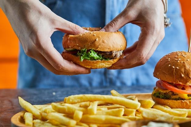 튀김 감자, 케첩, 마요네즈와 치즈 버거를 들고 여자 손