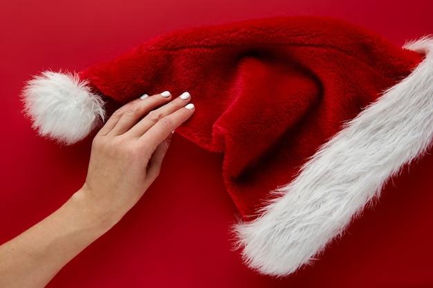 赤い背景にお祝いコロナウイルスサンタクロースの帽子を持っている女性の手。フラットレイ、トップビューのクリスマス休暇の構成。新年の壁紙バナー