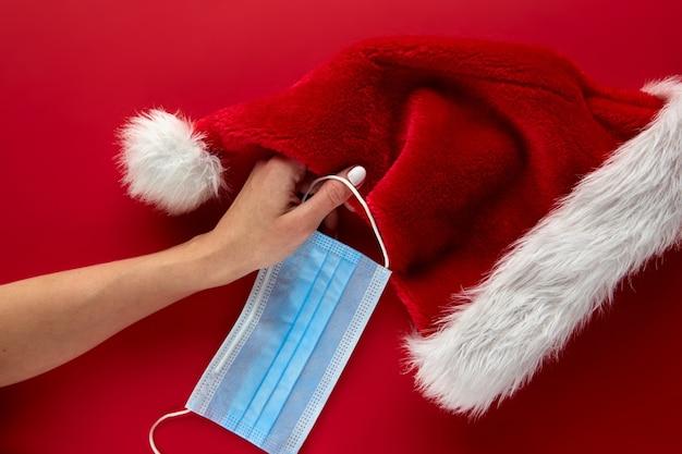 赤い背景にフェイスマスクと装飾が施されたお祝いコロナウイルスサンタクロースの帽子を持っている女性の手。フラットレイ、トップビューのクリスマス休暇の構成。新年の壁紙バナー