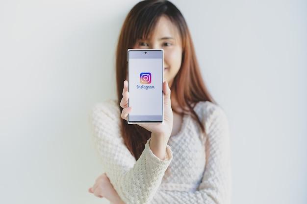 Instagram 응용 프로그램의 로그인 화면과 함께 삼성 노트 10 플러스를 들고 여자 손.