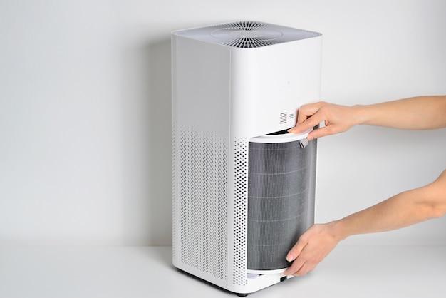Женщина, превращающая фильтр очистителя воздуха в новый, заменила новый фильтр в очистителе воздуха предотвращение аллергии pm 25 грязный воздушный фильтр требует обслуживания