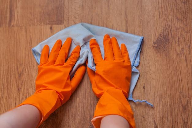 青いぼろきれを使って女性の手が木の床を拭きます。